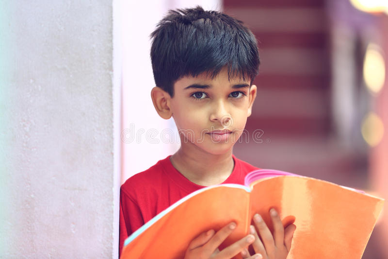 Indiano Little Boy com livro de texto imagens de stock