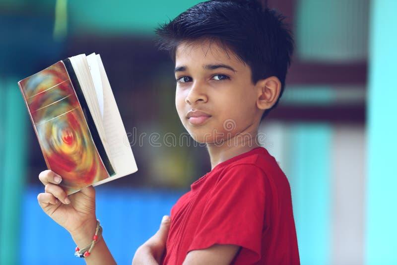 Indiano Little Boy com livro de texto fotografia de stock