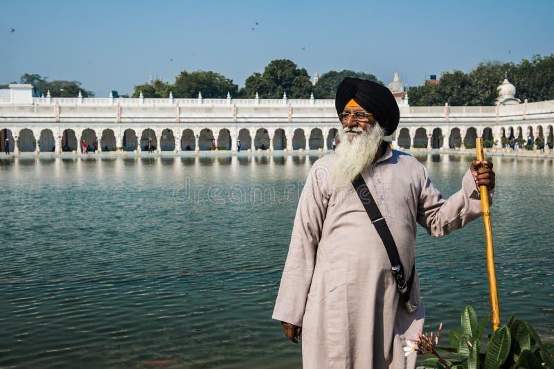 Indiano orgulhoso Um homem de Deli, Índia contemplando perto da água santamente de Gurudwara Bangla Sahibat imagens de stock royalty free