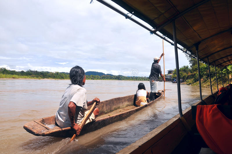 Indians overtakes tourist canoe, Rio Napo stock image
