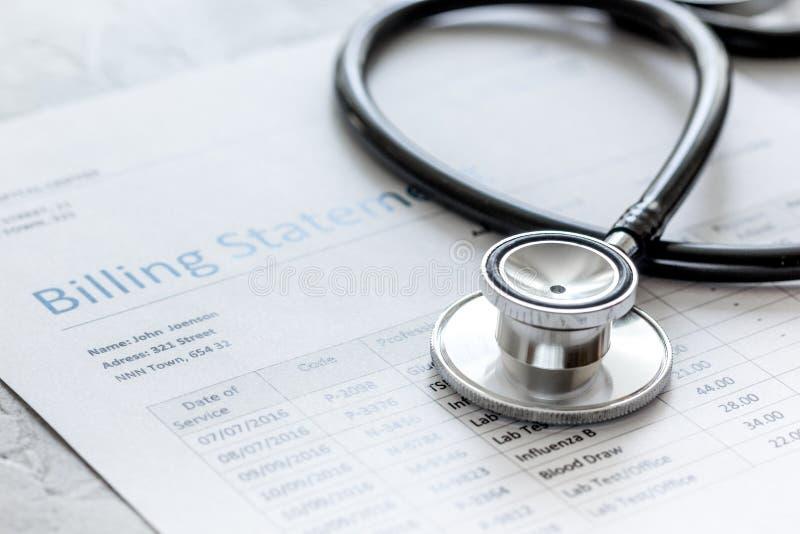 Indicação do faturamento dos cuidados médicos com o estetoscópio do ` s do doutor no fundo de pedra imagem de stock royalty free