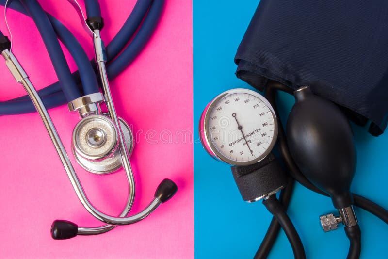Indicador de la presión arterial o sphygmomanometer y estetoscopio médico en fondo de dos colores: azul y rosa Concepto de la pre fotografía de archivo libre de regalías