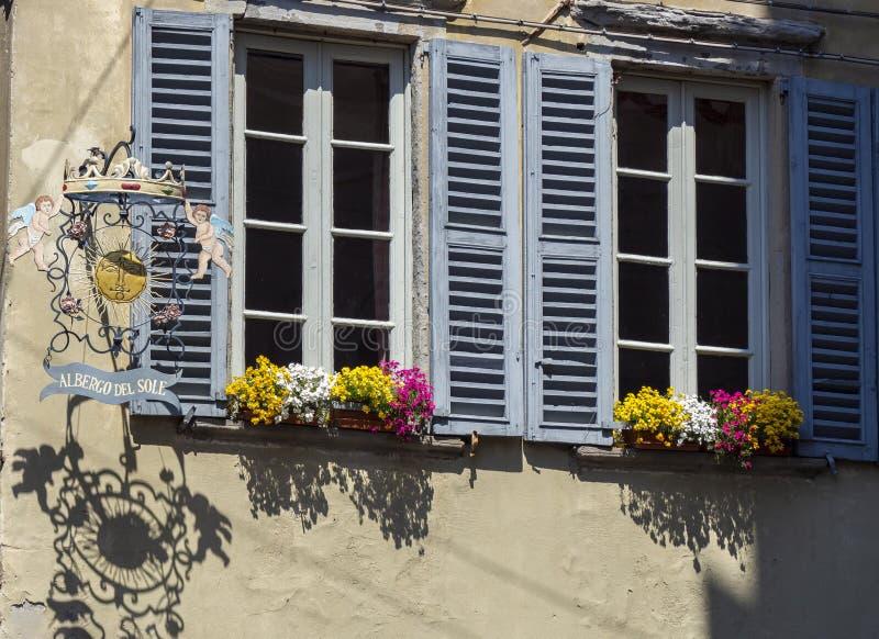 Indicador decorativo de um tenement hist?rico Vistas das ruas da cidade velha Sinal e janelas velhos do metal com flores imagem de stock royalty free