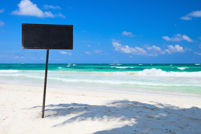 Indicador em branco do quadro-negro na praia tropical foto de stock royalty free