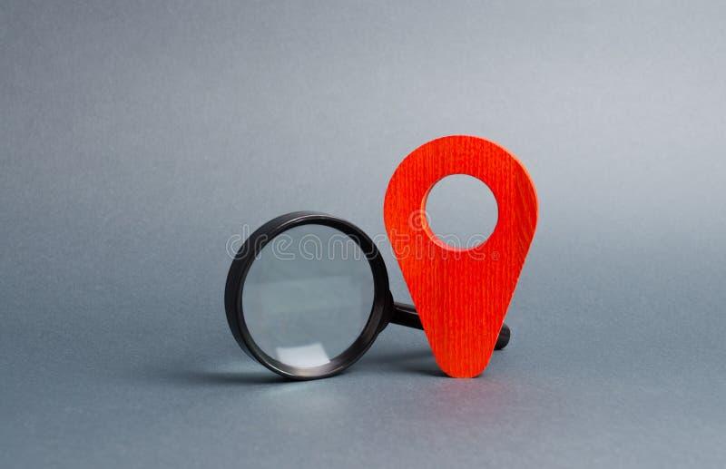Indicador rojo de la ubicación y una lupa en un fondo gris con el foco en los prism?ticos Espionaje en los ciudadanos Orientación imágenes de archivo libres de regalías