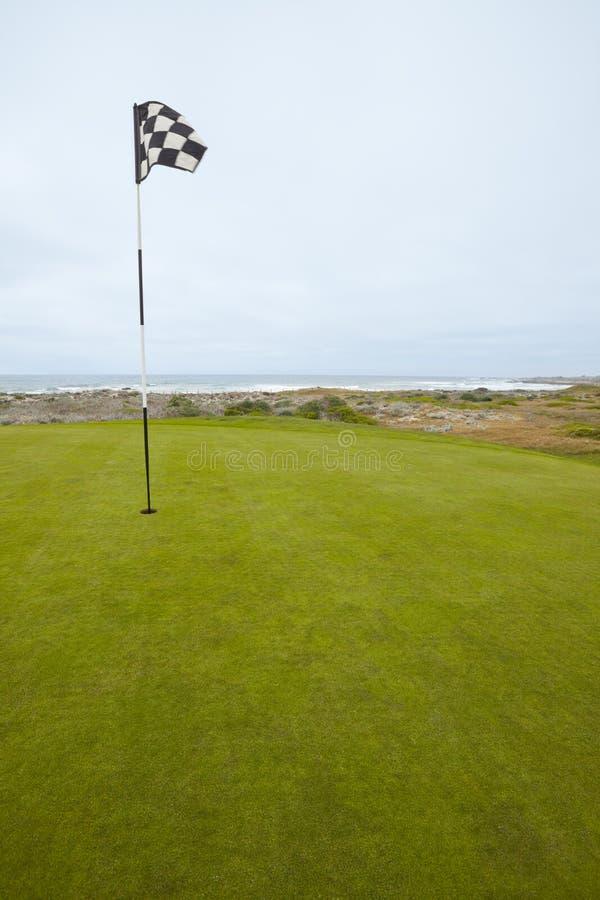 Indicador y verde que pone en campo de golf costero foto de archivo
