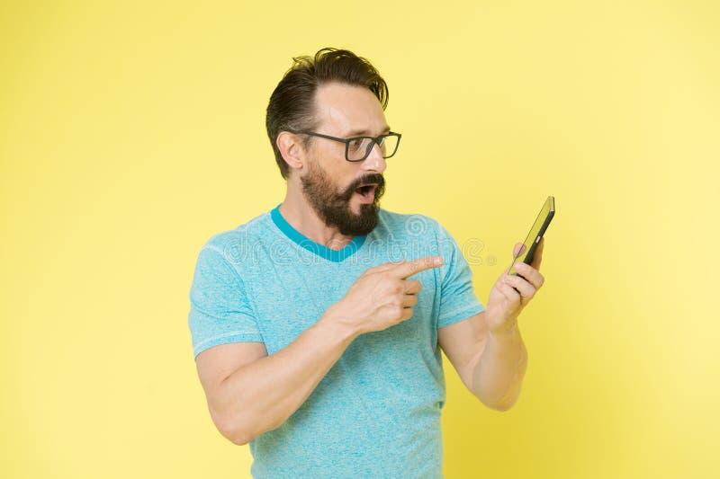 Indicare allegro degli occhiali del tipo allo smartphone Applicazione interattiva dell'utente felice dell'uomo per lo smartphone  fotografia stock libera da diritti