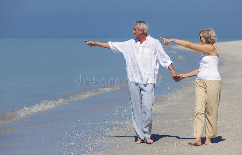 Indicare di camminata delle coppie senior felici tenendosi per mano spiaggia immagine stock libera da diritti