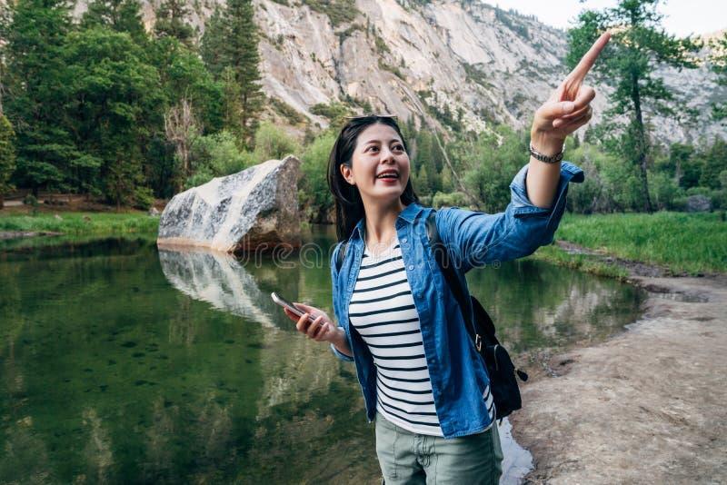 Indicare eccitato donna allegra della viandante il cielo fotografia stock