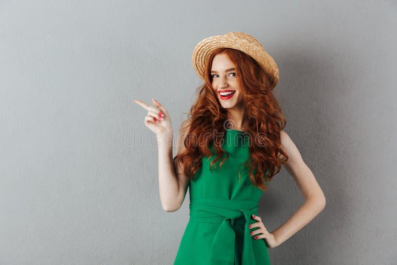 Indicare felice della giovane donna della testarossa immagine stock