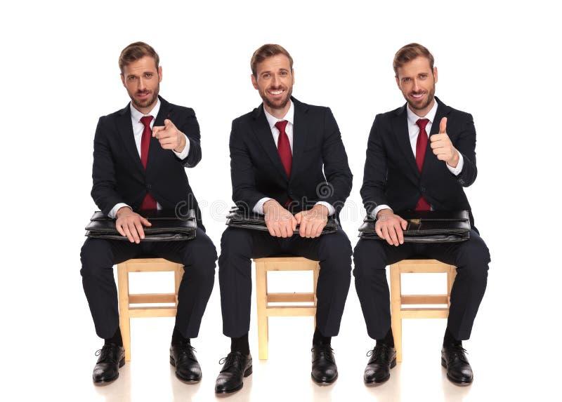 Indicare sorridente del giovane uomo d'affari e fare segno giusto immagine stock