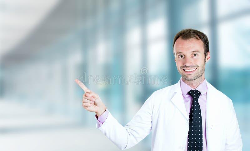 Indicare sorridente di medico maschio felice con il dito via su fotografie stock