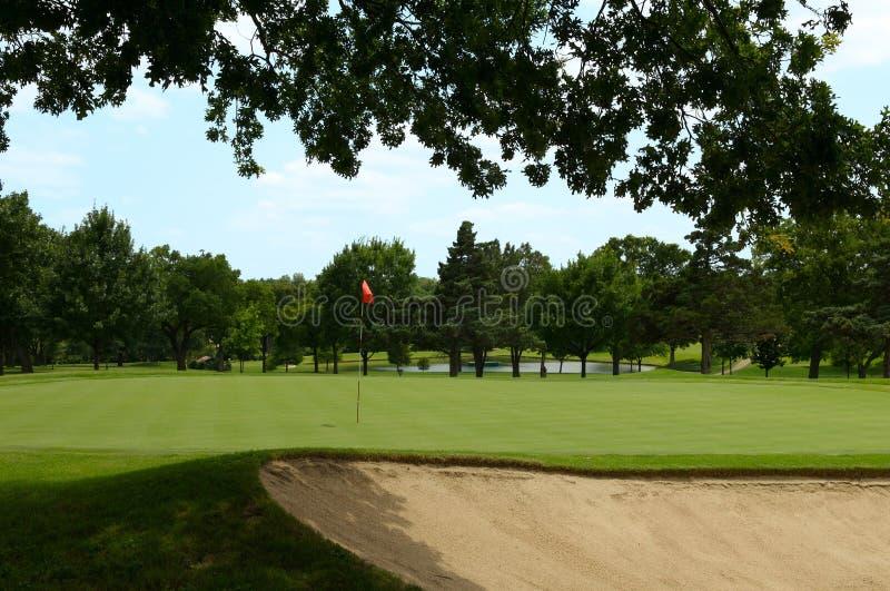 Indicateur rouge sur le vert de golf images stock