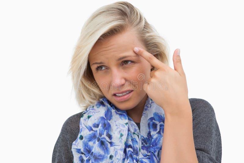 Indication blonde inquiétée le front photographie stock libre de droits