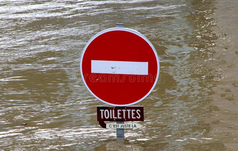 Indicator sign submerged by waters. Sign indicating toilets submerged by the waters, floods of the Seine, France stock image