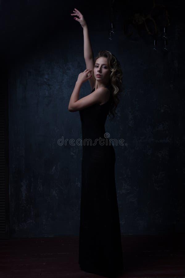 Indicatore luminoso scuro Una ragazza in un bello di sera vestito d'annata dal nero di lunghezza con un'acconciatura elegante che immagini stock libere da diritti