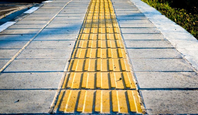 Indicatori gialli del marciapiede per i pedoni ciechi fotografia stock libera da diritti