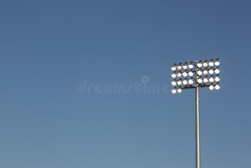 Indicatori luminosi dello stadio su una priorità bassa del cielo blu fotografia stock
