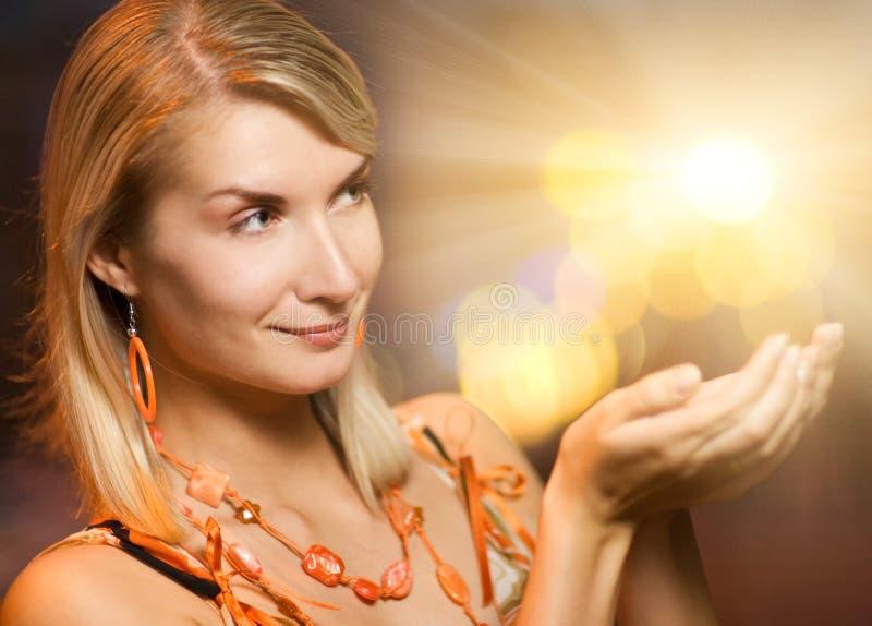 Indicatori luminosi di magia della holding della donna fotografie stock