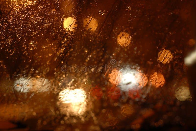 Indicatori luminosi di notte attraverso la finestra bagnata fotografia stock