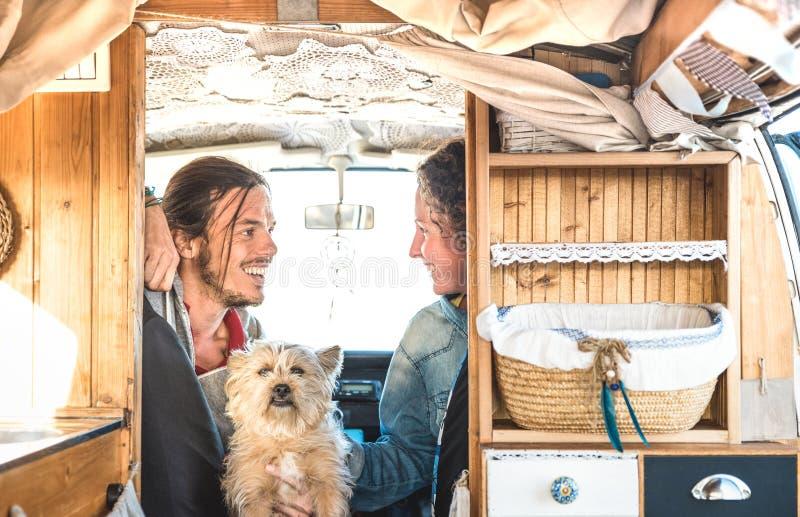 Indie Paare mit wenigem Hund, der zusammen auf Oldtimerminipackwagentransport - Reiselebensstilkonzept mit Hippie-Leuten reist stockfotos