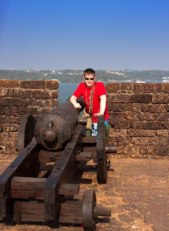 Indien goa Der Jugendliche nahe einem Gewehr auf einer Wand eines alten Forts lizenzfreies stockfoto