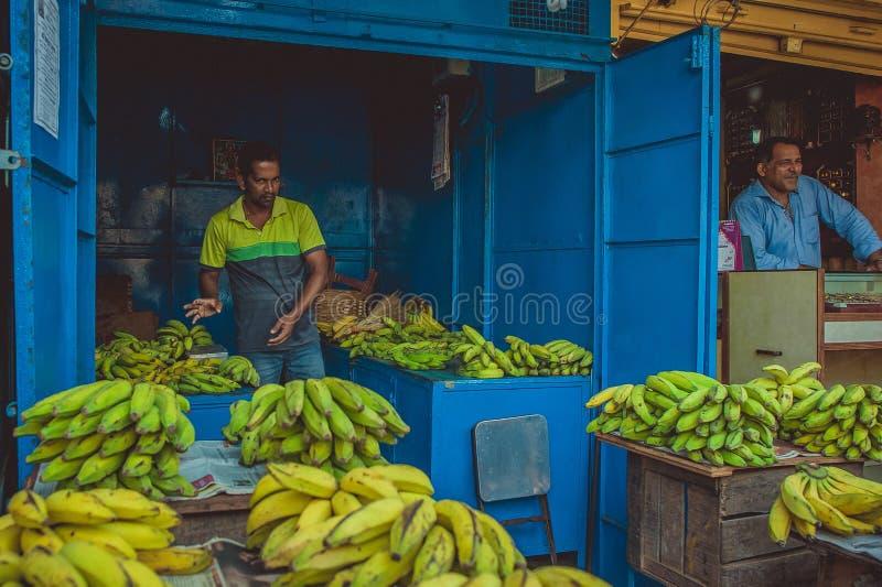 Indien Goa - Februari 9, 2017: Mannen i en blått shoppar sälja bananer fotografering för bildbyråer
