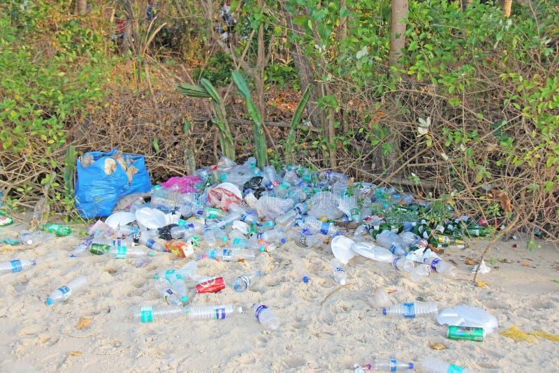 Indien Goa, Februari 05, 2018 Tomma plast- och glasflaskor ligger på stranden och förorenar ekologin av havet royaltyfria foton