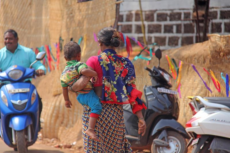 Indien GOA, Januari 28, 2018 Den fattiga indiska kvinnan med behandla som ett barn i hennes armar india armod arkivbild