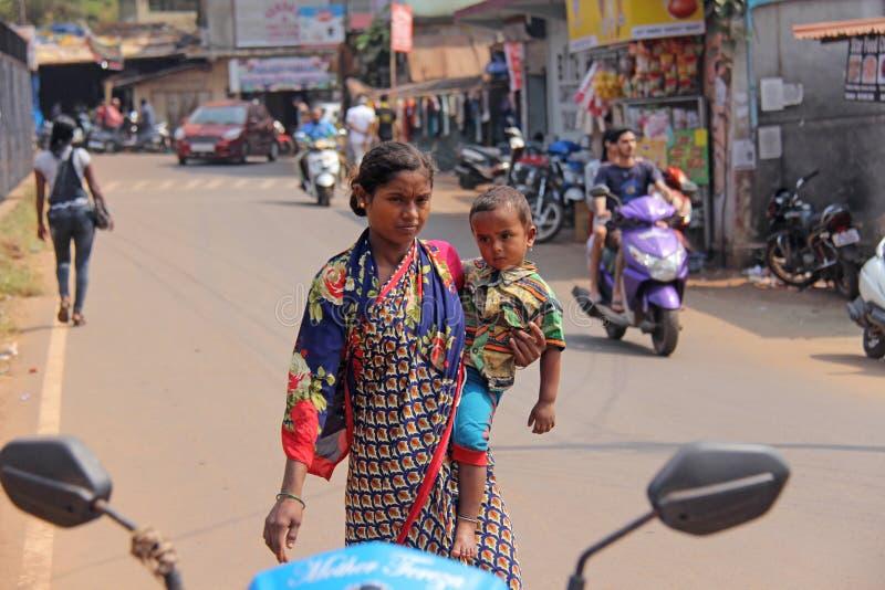 Indien GOA, Januari 28, 2018 Den fattiga indiska kvinnan med behandla som ett barn i hennes armar india armod royaltyfri foto