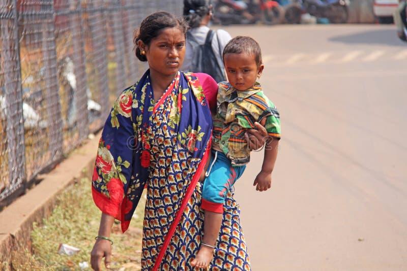 Indien GOA, Januari 28, 2018 Den fattiga indiska kvinnan med behandla som ett barn i hennes armar india armod arkivfoto