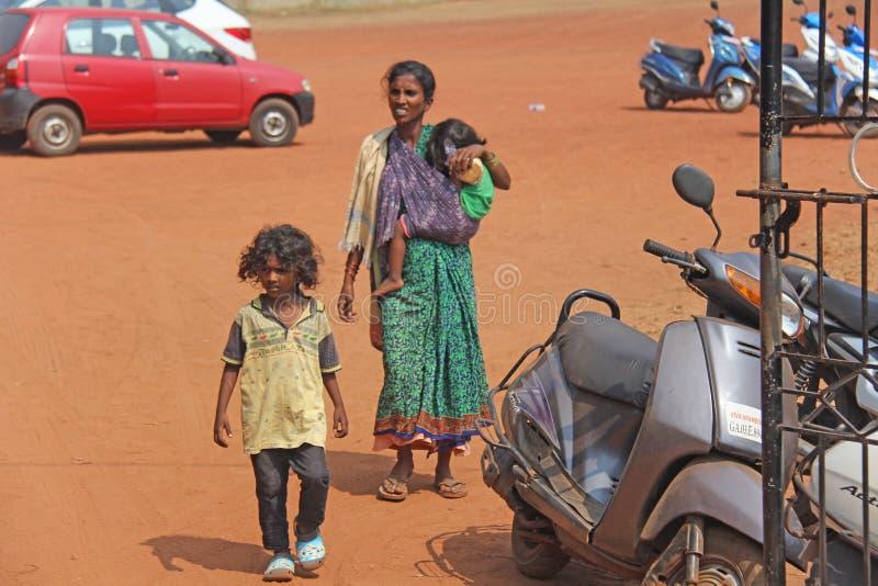 Indien GOA, Januari 28, 2018 Den fattiga indiska kvinnan med behandla som ett barn i hennes armar india armod arkivfoton