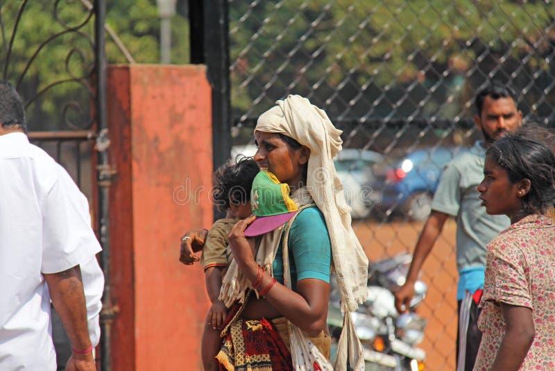 Indien GOA, Januari 28, 2018 Den fattiga indiska kvinnan med behandla som ett barn i hennes armar india armod fotografering för bildbyråer