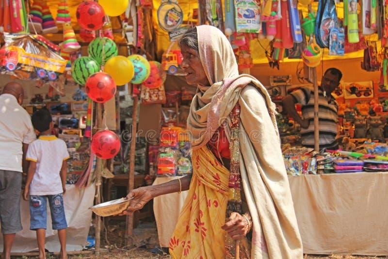 Indien GOA, Januari 28, 2018 Den fattiga kvinnan frågar för pengar på gatan i Indien En tiggarekvinna med en utsträckt hand armod arkivbilder