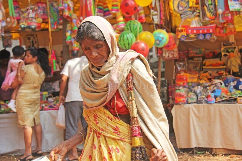 Indien GOA, Januari 28, 2018 Den fattiga kvinnan frågar för pengar på gatan i Indien En tiggarekvinna med en utsträckt hand armod arkivfoto