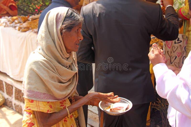 Indien GOA, Januari 28, 2018 Den fattiga kvinnan frågar för pengar på gatan i Indien En tiggarekvinna med en utsträckt hand armod royaltyfri fotografi