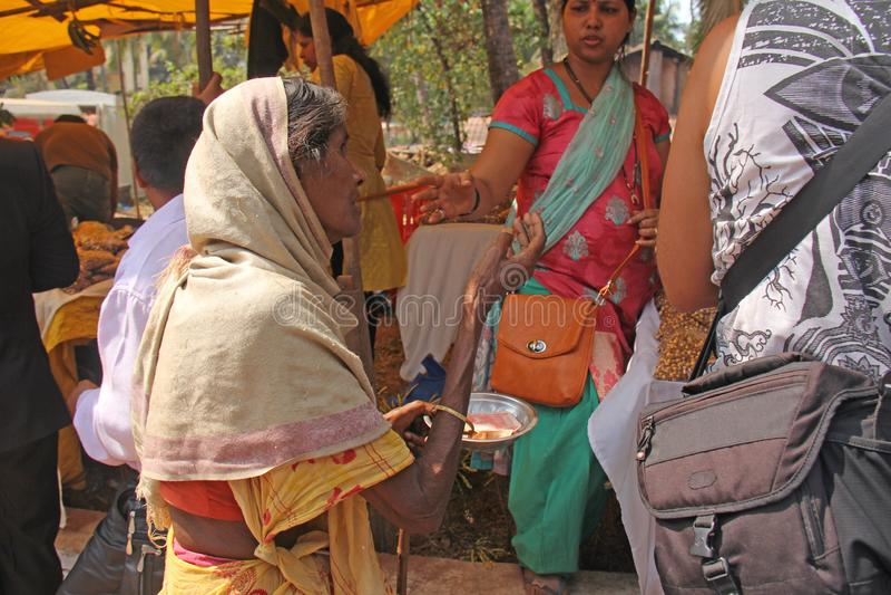 Indien GOA, Januari 28, 2018 Den fattiga kvinnan frågar för pengar på gatan i Indien En tiggarekvinna med en utsträckt hand armod fotografering för bildbyråer