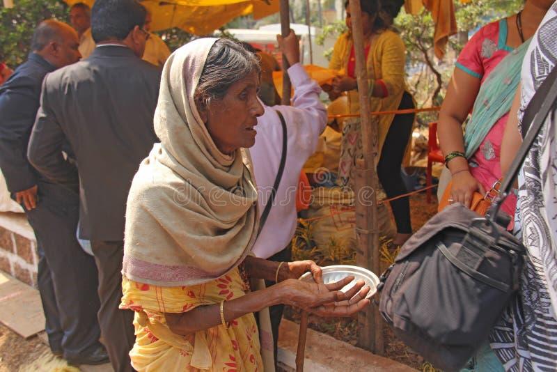 Indien GOA, Januari 28, 2018 Den fattiga kvinnan frågar för pengar på gatan i Indien En tiggarekvinna med en utsträckt hand armod royaltyfri foto