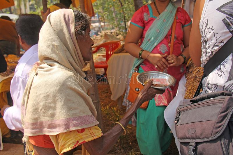 Indien GOA, Januari 28, 2018 Den fattiga kvinnan frågar för pengar på gatan i Indien En tiggarekvinna med en utsträckt hand armod royaltyfria bilder