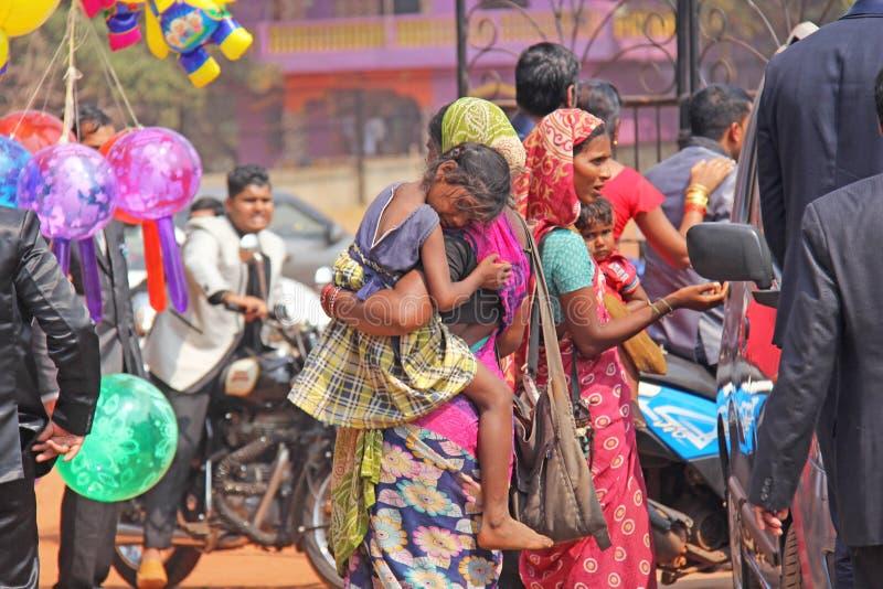Indien GOA, Januari 28, 2018 Den fattiga kvinnan med behandla som ett barn i hennes armar Kvinnan är en tiggare india armod royaltyfria bilder