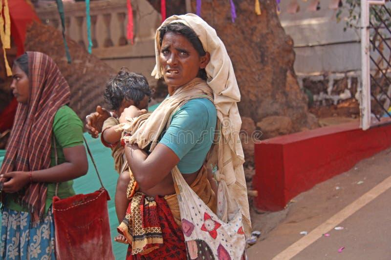 Indien GOA, Januari 28, 2018 Den fattiga kvinnan med behandla som ett barn i hennes armar Kvinnan är en tiggare india armod royaltyfri foto