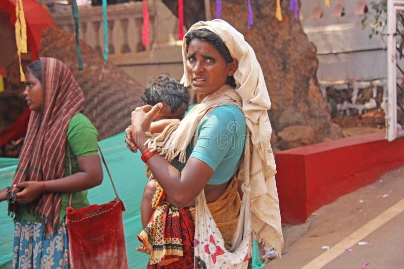 Indien GOA, Januari 28, 2018 Den fattiga kvinnan med behandla som ett barn i hennes armar Kvinnan är en tiggare india armod arkivfoto