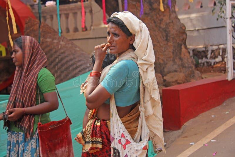 Indien GOA, Januari 28, 2018 Den fattiga kvinnan med behandla som ett barn i hennes armar Kvinnan är en tiggare india armod arkivbild