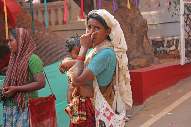 Indien GOA, Januari 28, 2018 Den fattiga kvinnan med behandla som ett barn i hennes armar Kvinnan är en tiggare india armod arkivfoton