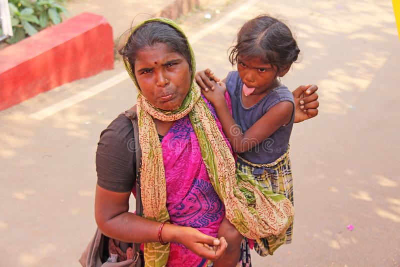 Indien GOA, Januari 28, 2018 Den fattiga kvinnan med ett barn frågar för pengar på gatan i Indien En tiggarekvinna med ett utsträ royaltyfria foton