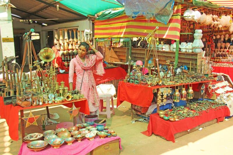 Indien Goa Januari 24, 2018 En kvinna säljer hennes gods på marknaden royaltyfria bilder
