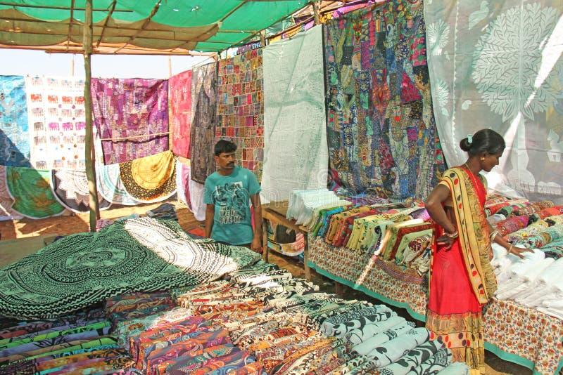 Indien GOA, Januari 24, 2018 Indisk marknad i byn av Anjuna Ljusa gods och målarfärger av Indien Säljare säljer deras royaltyfri foto