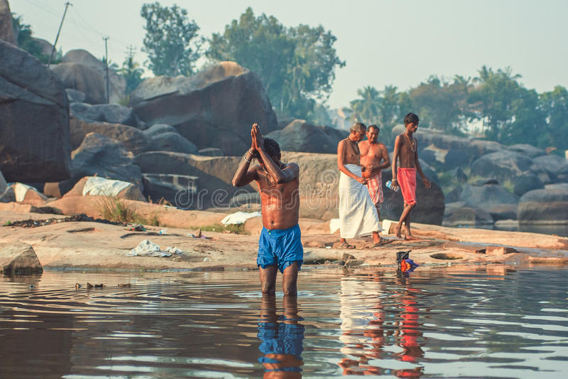 Indien, Hampi - 22. Dezember 2015: Ein Mann betet im Fluss, der im Wasser kniehoch steht stockfotografie