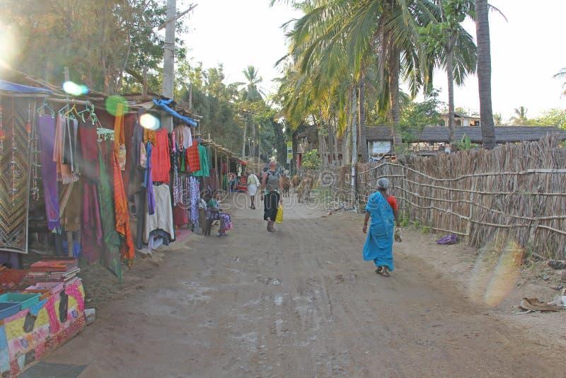 Indien, Hampi, am 2. Februar 2018 Die Hauptstraße des Dorfs von Virupapur Gaddi Leben, Wirtschaft, Touristen, Kühe, der Markt, stockfotos