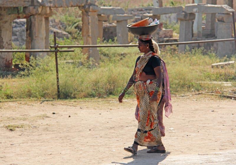 Indien, Hampi, am 2. Februar 2018 Eine indische Frau in einem Sari trägt eine schwere Last auf ihrem Kopf Weibliche Arbeit in Ind stockfoto